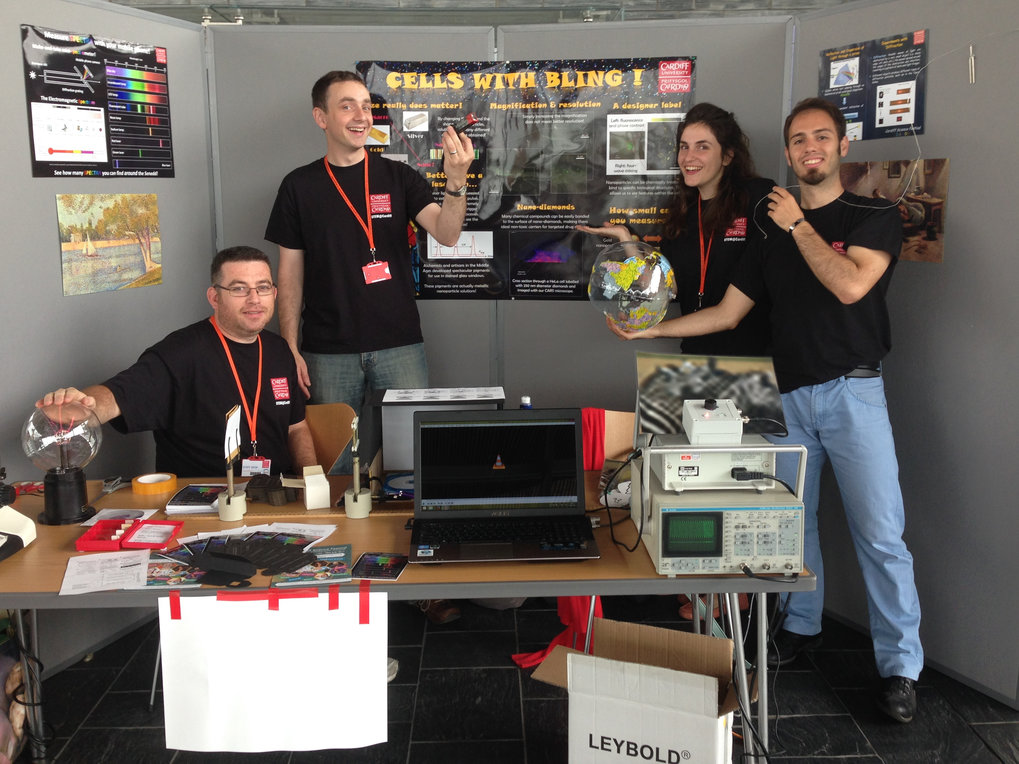 "Date: 20.07.2014 Location: Cardiff, Wales, UK  Participant(s): Attilio Zilli, Naya Giannakopoulou  Description: Attilio and Naya had a stand, engaged the visitors with scientific demonstrations, and presented the poster ""Cells with Bling""."